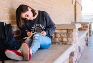 Brown Haired Caucasian teen girl wearing gray sweatshirt, torn jeans, and airpods, sitting on concrete bench writing in book.